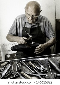 Old shoemaker repair the sole of a shoe.