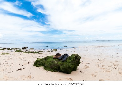 Old shoes on the big stone with moss. Small rocks scattered on beach sand close up. Beautiful ocean landscape, amazing sky. Bali, Indonesia.