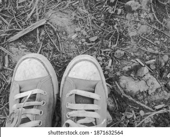 Old shoes stained with dusty dirt on the ground.
