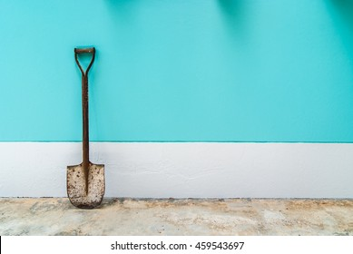 old shovel with mint, cyan pastel cement wall background