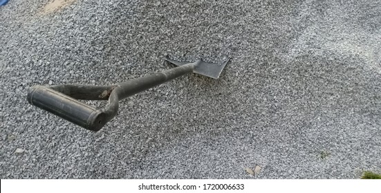 Old shovel put on a small stone in construction area.