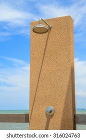Old shower head on stone with sea and blue sky background