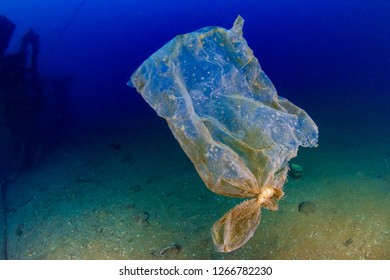 An old, shredded plastic bag drifting underwater in the ocean next to an old shipwreck