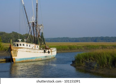 An old shrimp boat docked in a marshy grassland
