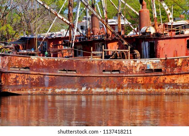 Old shrimping boats anchored and abandoned gathering rust at port.