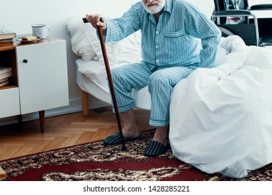 Old sick man with grey beard and hair wearing blue pajamas and sitting on bed at home