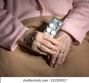 Old sick woman with pills at home