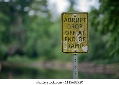 "Old sign with ""abrupt drop off at end of ramp"" covered in moss and dust."