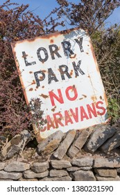 An old sign at the entrance to a lorry park, with the instruction that no caravans are allowed.