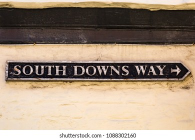 An old sign on the side of a building  in Alfriston, Sussex, directing towards The South Down Way