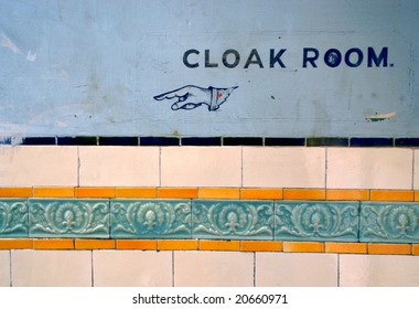 old Sign pointing to the cloak room, with vintage tiles below