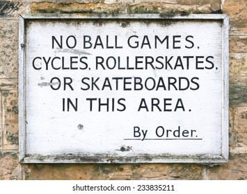Old sign prohibiting ball games, cycling, roller skates and skateboarding on a stone wall background