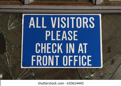 Old sign that says, ALL VISITORS PLEASE CHECK IN AT FRONT OFFICE.
