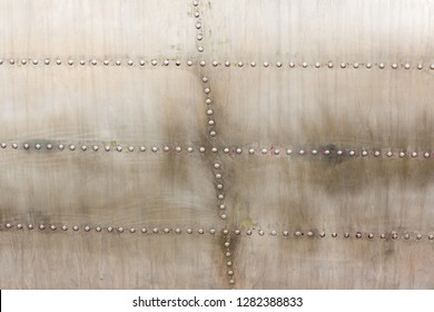 Old silver metal surface of the aircraft fuselage with rivets. Iron plate,steel sheet texture,pattern and background. Aluminum surface of the aircraft fuselage. Smooth rows of rivets.