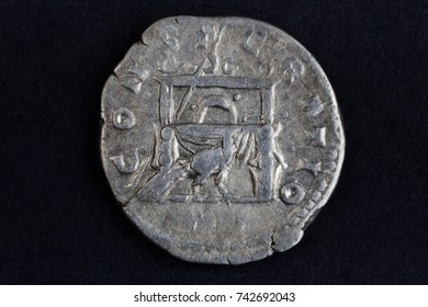 old silver roman coins on a black background