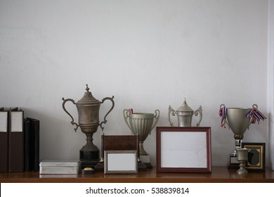 Old silver trophies, picture frames and file folders on a sideboard cabinet in an retro style office.