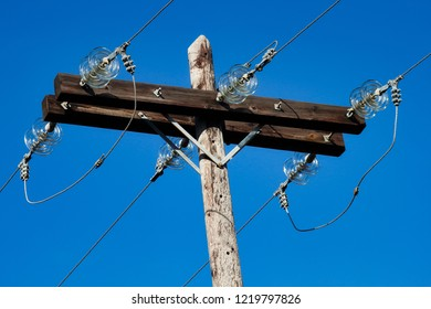 Old simple rural weathered wooden utility pole with parallel cables and insulators on blue sky