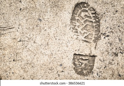 The old single imprint,footprint of shoe or boot on concrete with copy space,on vintage tone
