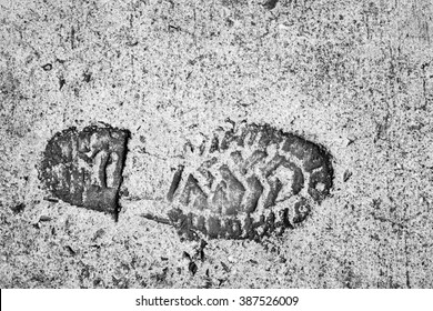 The old single imprint,footprint of shoe or boot on concrete with copy space,on black and white color