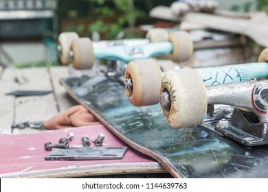 6611423a Old skateboard with wheels lies for repair on a wooden table outdoors.