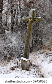 Old skew wooden cross covered with snow