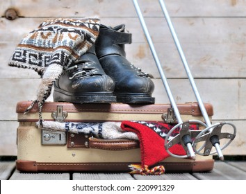 old ski boots on a small  suitcase full of warm clothes