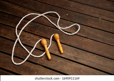 An old skipping rope on a wooden deck. Exercising at home concept image.