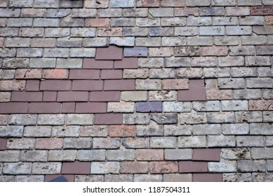 An old slate roof with some repairs in need of more or replacement.