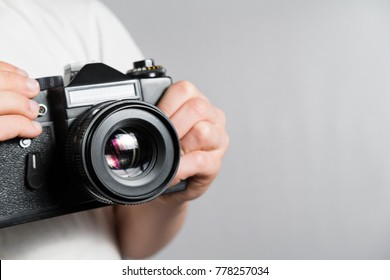 old SLR film camera in the hands of a child in a white t-shirt