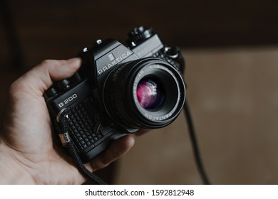 Old SLR Vintage camera Praktica B200 hold in hand by man. Wroclaw, Poland - October 22. 2019: 35mm film made by German company Pentacon between 1983 and 1985.