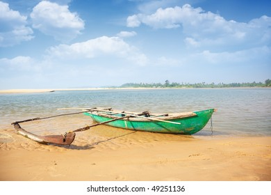Old small boat at the tropical beach in India. Vibrant colors