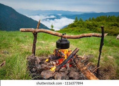 Old small kettle is heated on a bonfire on a green mountain meadow during a bad weather. Epic travel in the mountains.