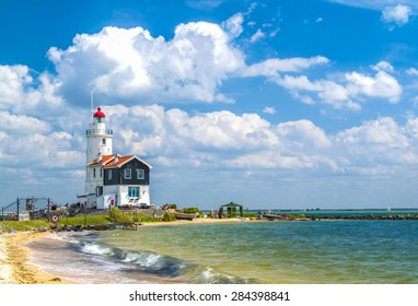 Old and small Lighthouse in seaside with nice beach and clouds. (North Holland)