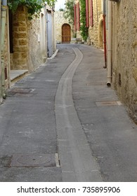 Old small pedestrian street with tall typical stone buildings in a Southern village in France