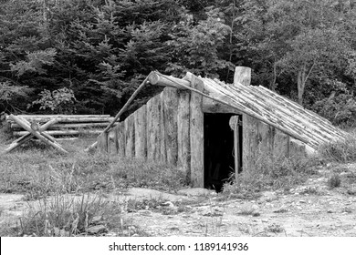 An old, small pit house made from logs. This is the primitive type of pit house that was built by people who escaped slavery in the United States and came to Canada. Black and white.