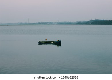 An old small row boat half sunken in a salt marsh tidal estuary with two buoys near it. Deep blue and green water on a over cast grey day in winter in northern England.
