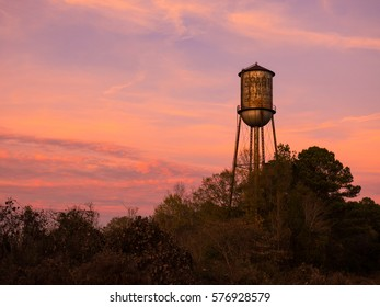 Old small town water tower against a brilliant sunset sky.