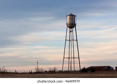 Old small town water tower, lit by sunlight from the left side and set against a cloudy sky at dusk.