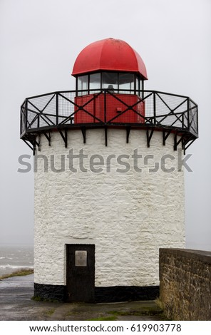 Old small white lighthouse in Burry Port Harbour in bad storm windy weather, Burry Port, Wales, UK