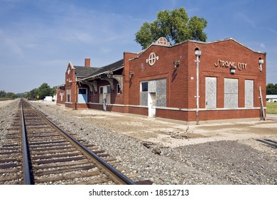 Old small-town railway station sits abandoned along a single track in Strong City, Kansas