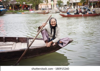 Old smiling elderly woman sailing canoe on the river in Vietnam.