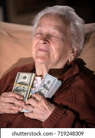 Old smiling gray-haired woman holding dollar cash money at home