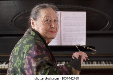 Old smiling lady pianist seating at the piano