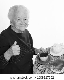 Old smiling woman having tea with nut roll  on a white background