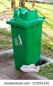 Old sneakers beside trash