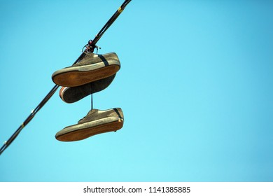 old sneakers hang on wires
