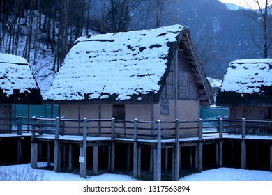 Old snow-covered mountain stilt houses
