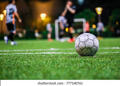 Old Soccer ball, Football on the grass line in soccer stadium at night with copy space and player with light background. goal,success concept.