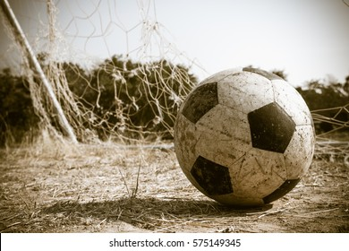 Old soccer ball on the field of rural Thailand, process color.