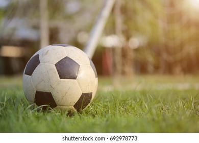 Old soccer ball on the grass